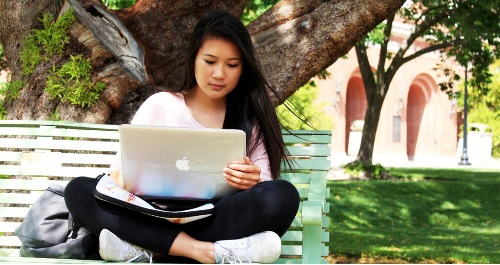 Student on bench with laptop