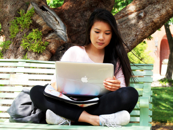 Girl with laptop on bench